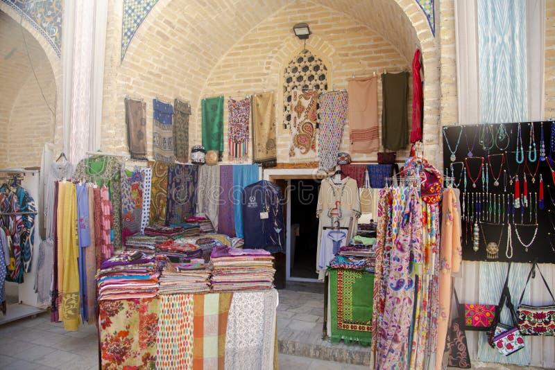 Bukhara Uzbekistan - mars 13, 2019: Den utomhus- gatan shoppar insidan av Nadir Divan-Begi Madrasah arkivfoto