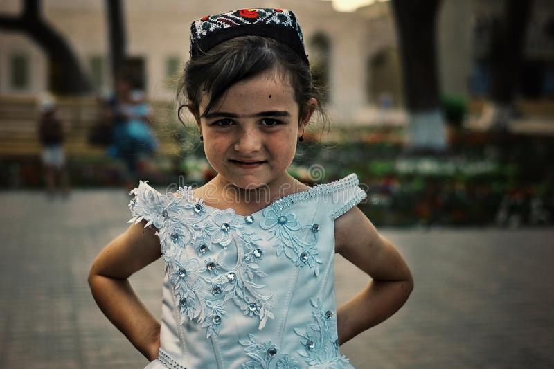 Young girl posing in traditional dress in the historical walled city of the silk road stock photo