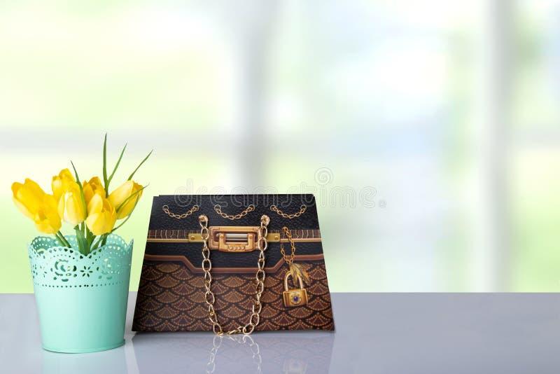 Bukietów żółci tulipany i brown prezenta papierowa torba na stole wewnątrz dla obraz royalty free