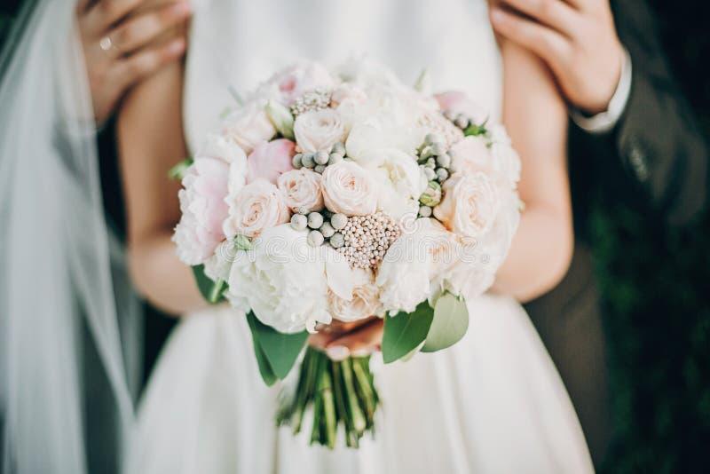 Nowoczesny bukiet ślubny w rękach panny młodej Stylowy pan młody łagodnie przytulając wspaniałe ramiona panny młodej w letnim par obraz stock