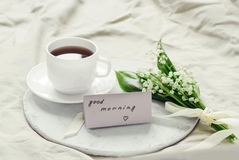 bukiet świeże leluje dolina, świeżo warzący dzień dobry na drewnianej tacy na łóżku, kawy i notatki zdjęcia stock