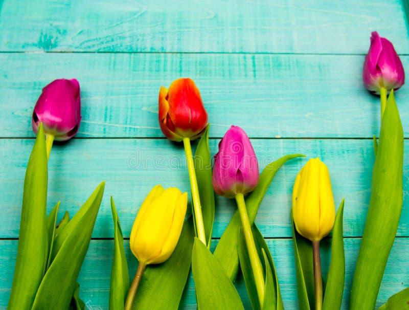 Bukiet żółci tulipany na drewnianym tle z kopertą, wiążący z faborek przestrzenią dla teksta fotografia royalty free