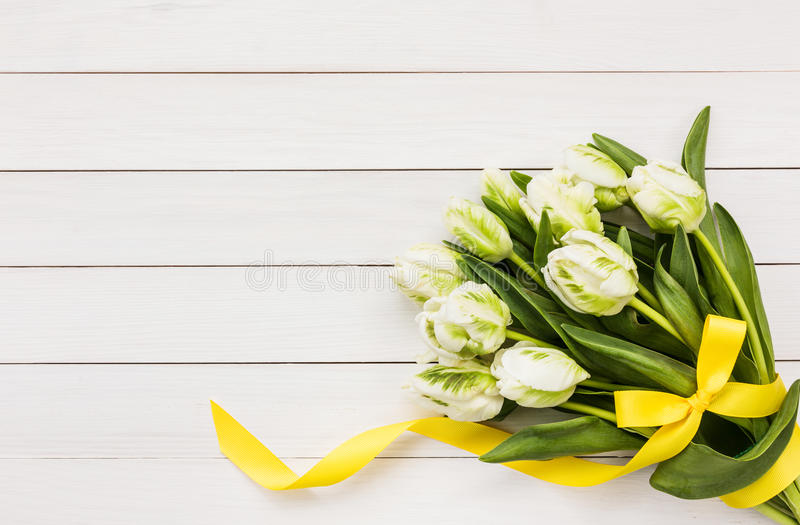 Bukiet biali tulipany dekorował z żółtym faborkiem na białym drewnianym tle obraz stock