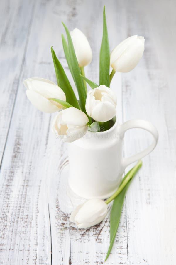Bukiet biali tulipany nad białym drewnianym stołem zdjęcie royalty free