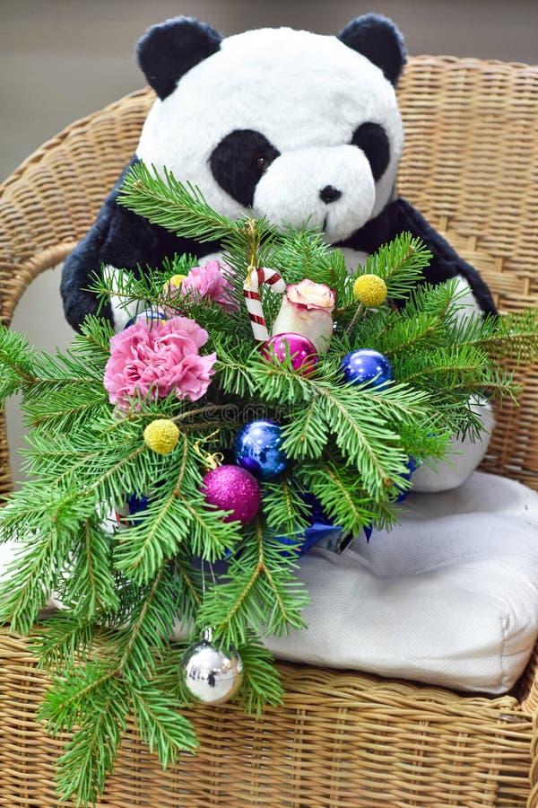 Bukiet choinka z Bożenarodzeniowymi dekoracjami i uroczymi kwiatami Na łozinowym krześle Zabawkarski niedźwiedź w tle zdjęcia royalty free