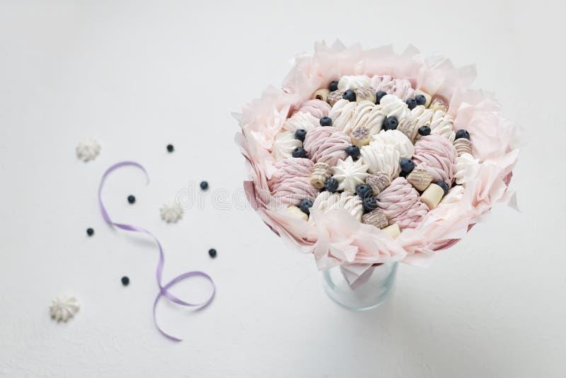 Bukiet cukierków stojaki w wazie przeciw tłu rozrzucone jagody i purpurowy faborek obrazy stock