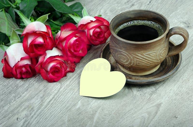 bukiet czerwone róże i filiżanka kawy na drewnianym stole Odgórny widok zdjęcia royalty free