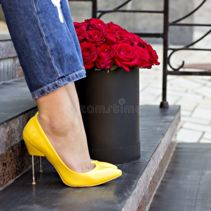 Bukiet czerwone róże i kobiet nogi obrazy stock
