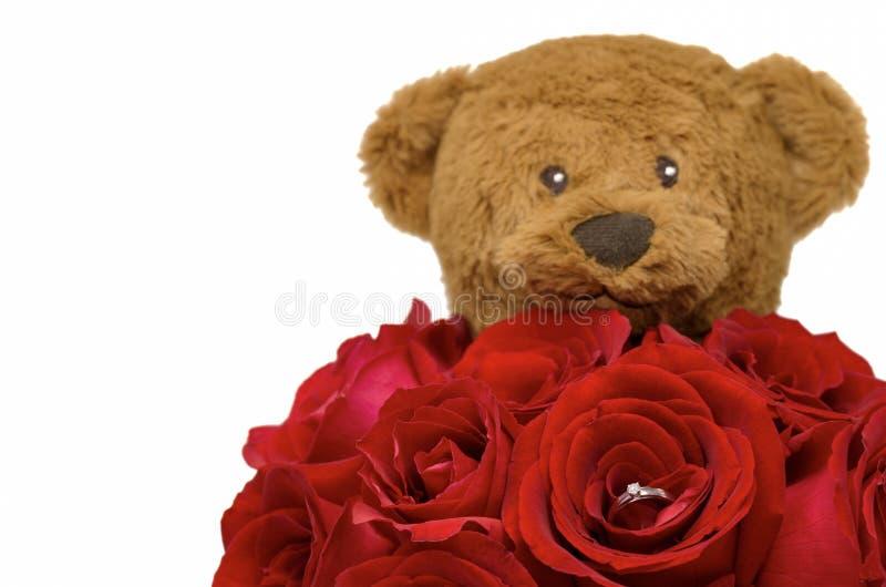 Bukiet czerwone róże które srebnego diamentowego pierścionek z wśrodku zamazanego misia fotografia stock