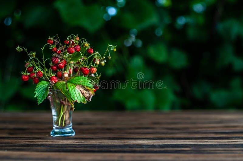 bukiet dzika truskawka w przejrzystym strzału szkle zostaje na brązu drewnianym stole z zielonymi liśćmi na plecy z placeholder, zdjęcia royalty free