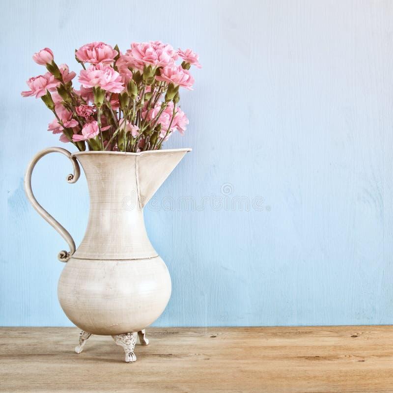Bukiet goździk kwitnie w rocznika bielu wazie fotografia royalty free