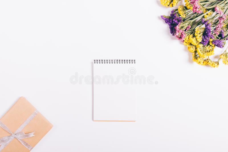 Bukiet kolorowi kwiaty, notatnik i pudełko z prezenta lying on the beach, zdjęcie stock