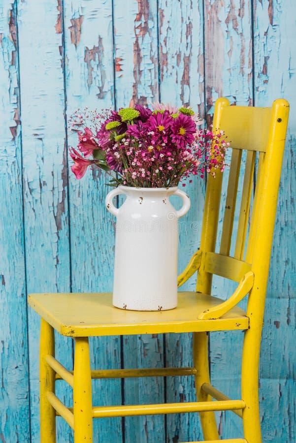 Bukiet kwiaty w rocznika wazowym obsiadaniu na żółtym krześle obraz royalty free