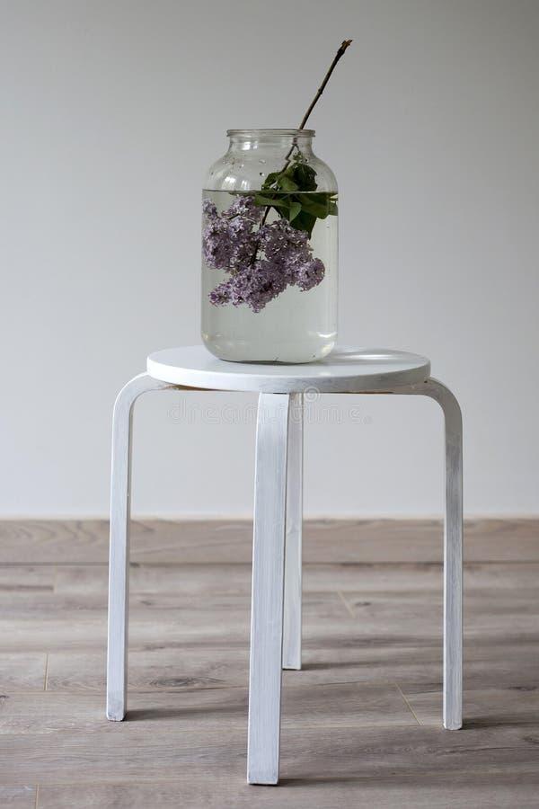 Bukiet lile gałązki w przejrzystym zielonym słoju na białym krześle jako dekoracja wnętrze obraz royalty free