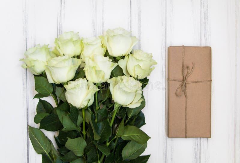 Bukiet luksusowe białe róże i przedstawia pudełko w eco papierze na białym drewnianym tle Odgórny widok, mieszkanie nieatutowy zdjęcia stock