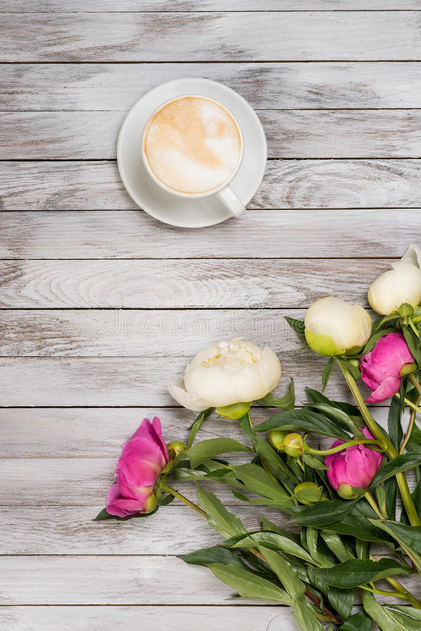Bukiet peonie i filiżanka kawy na lekkim drewnianym tle Odgórny widok zdjęcie royalty free