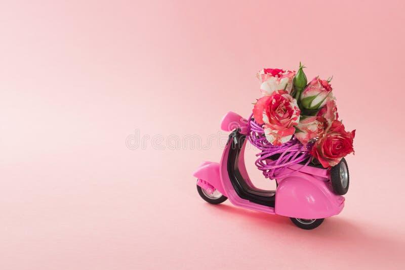 Bukiet róże kwitnie w koszu na tylnym siedzeniu śliczna różowa hulajnoga na różowym tle zdjęcia royalty free