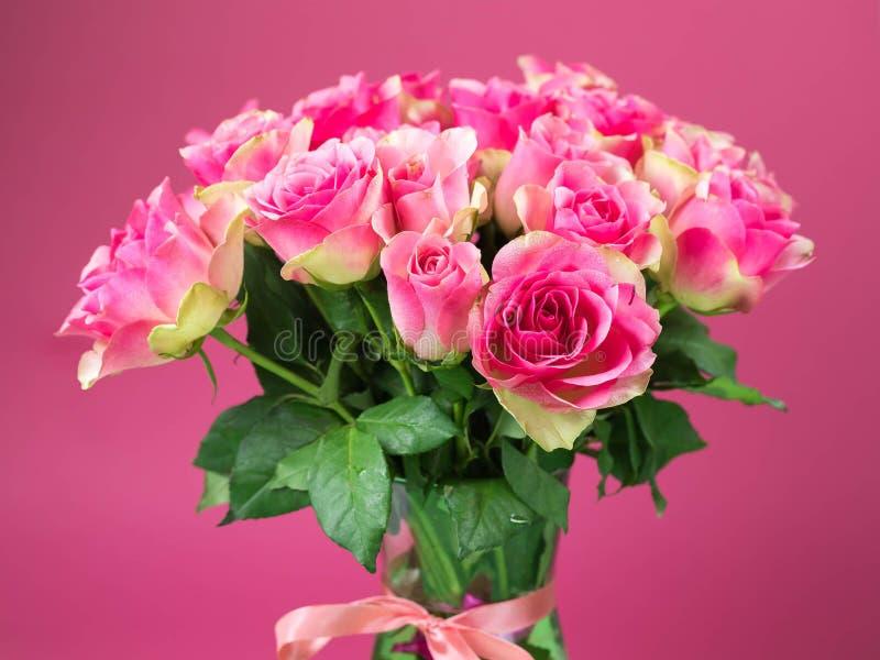 Bukiet różowe róże w szklanej wazie na różowym tle Na wazie czerwona taśma wiąże wodna kropla na różach obraz stock