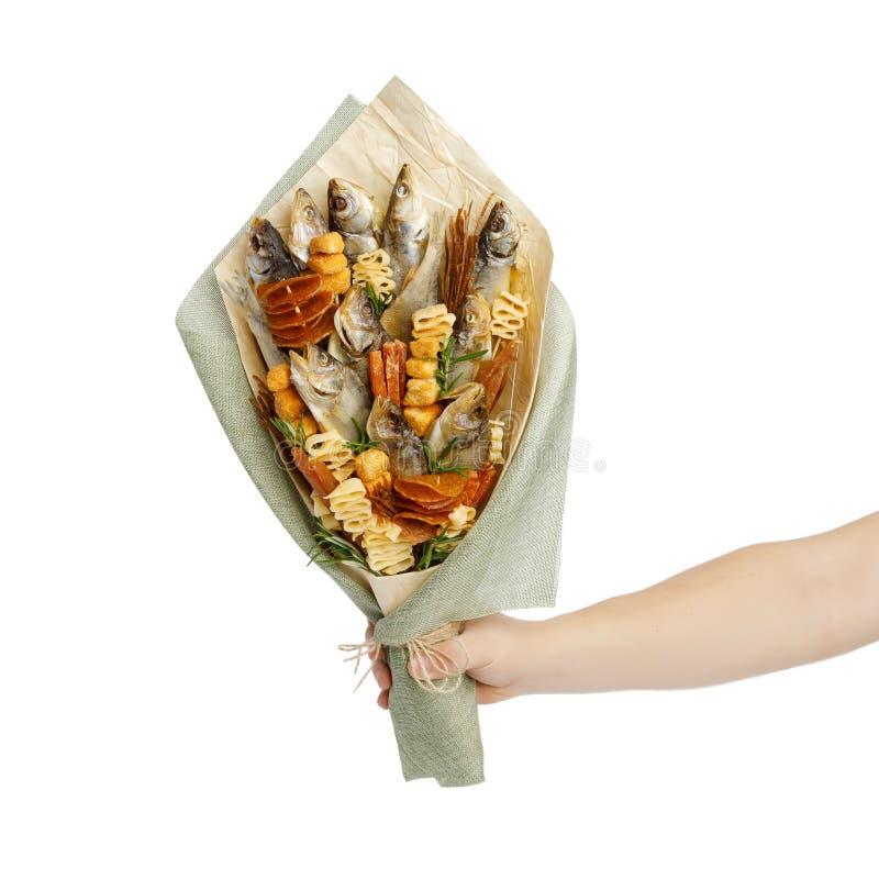 Bukiet składa się solonego sztokfisza różni trakeny, plasterki wysuszona kałamarnica i inną ryby, jest w męskiej ręce na białym p zdjęcie stock