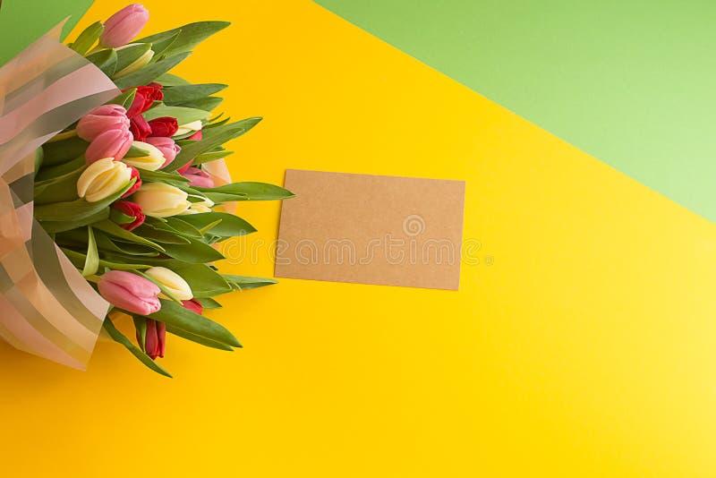 Bukiet stubarwni tulipany na żółtej zieleni geometrycznym textural tle obraz stock