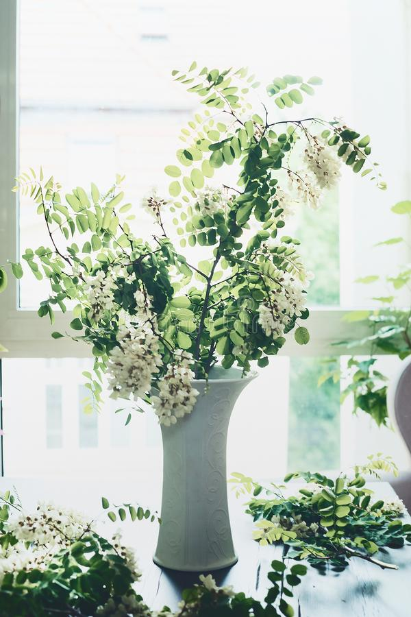 Bukiet z kwiecenia okwitnięciem rozgałęzia się w wazie na stole przy okno Wygodny domowy wnętrze i projekt zdjęcie royalty free