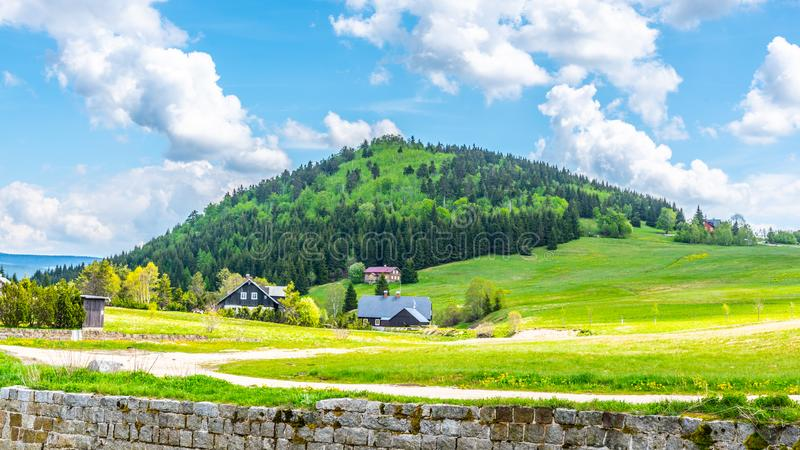 Bukovec mountain above Jizerka village. Summer landscape with green meadows, blue sky and white clouds. Jizera Mountains stock images