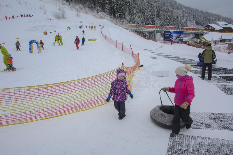 Bukovel, de Oekra?ne - December 26, 2018 De meisjes hebben pret op sneeuwdia's, berijden opblaasbare kamers en genieten van de ve royalty-vrije stock fotografie