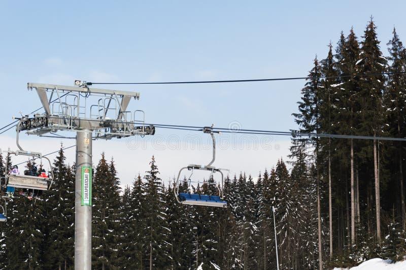 BUKOVEL UKRAINA - FEBRUARI 28, 2018 sidosikt av det gråa chairlifttornet i skidasemesterorten Bukovel, Ukraina fotografering för bildbyråer