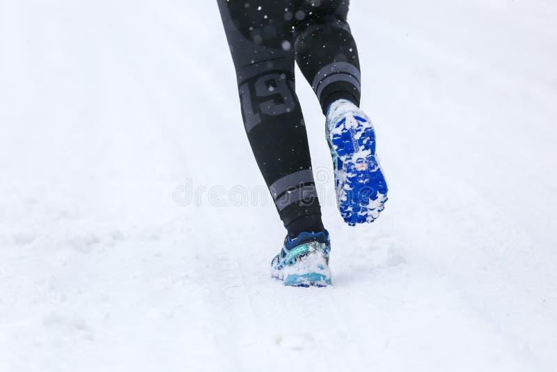 BUKOVEL UKRAINA - MARS 20: Kvinnlign lägger benen på ryggen i spring för Salomon speedcross 4 GTX på vintervägen royaltyfri bild