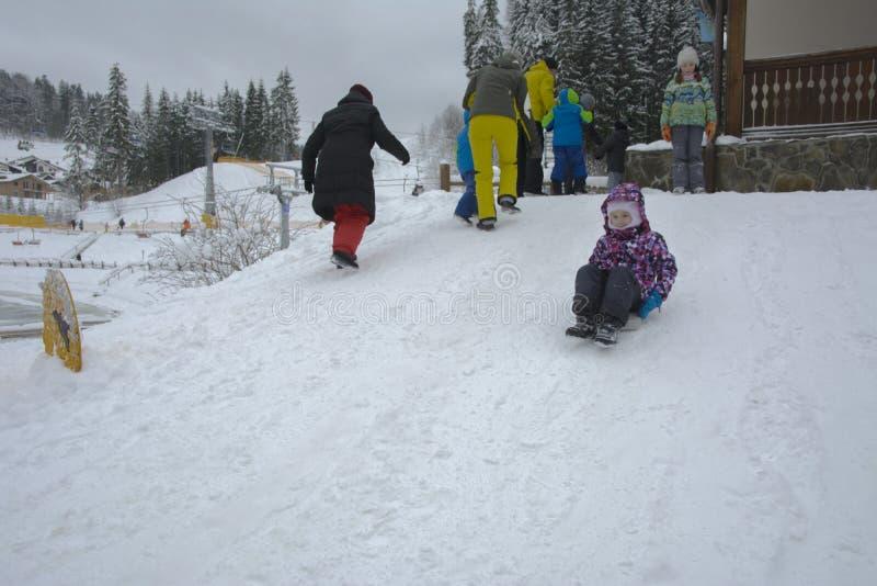 Bukovel, Ukraine - December 26, 2018. One little girl is having fun on a snow slide and enjoying fresh snow on a beautiful winter royalty free stock photos