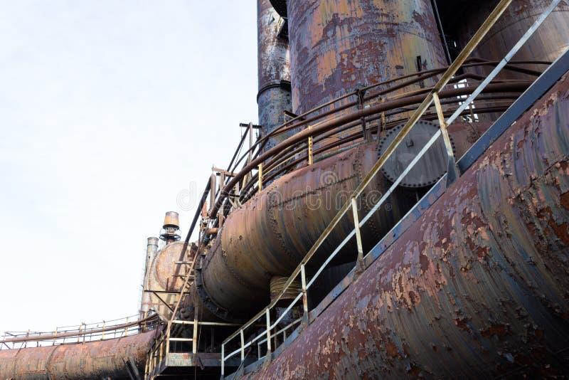 Buktade industriella rör och rör av gammalt stålsätter maler med tung polityr av rost, kopieringsutrymme arkivbild