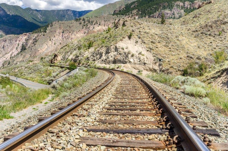 Buktig järnvägsspår i ett berglandskap royaltyfri bild