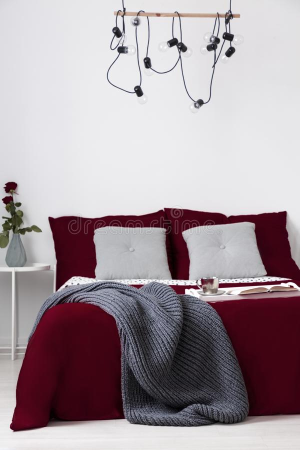 Bed dressed in red wine pillows and cover in a simple bedroom interior. Real photo. stock photo