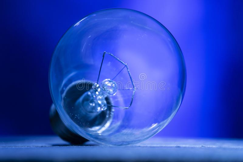Bulb with clear glass, on a blue background stock photography