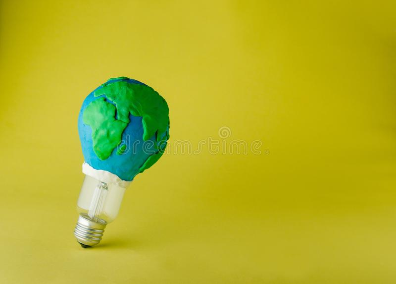Bulb decorated as plasticine Earth planet model on yellow background royalty free stock images