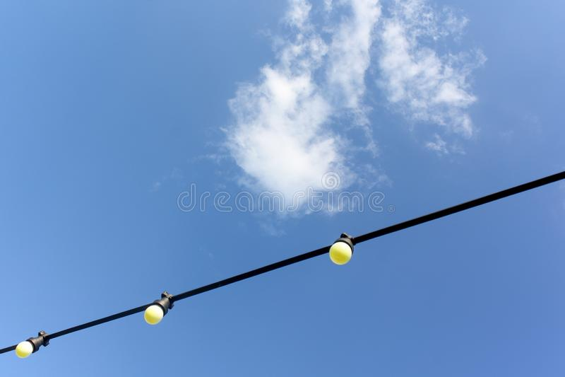 Bulb electricity wire outside. Blue sky background royalty free stock photos