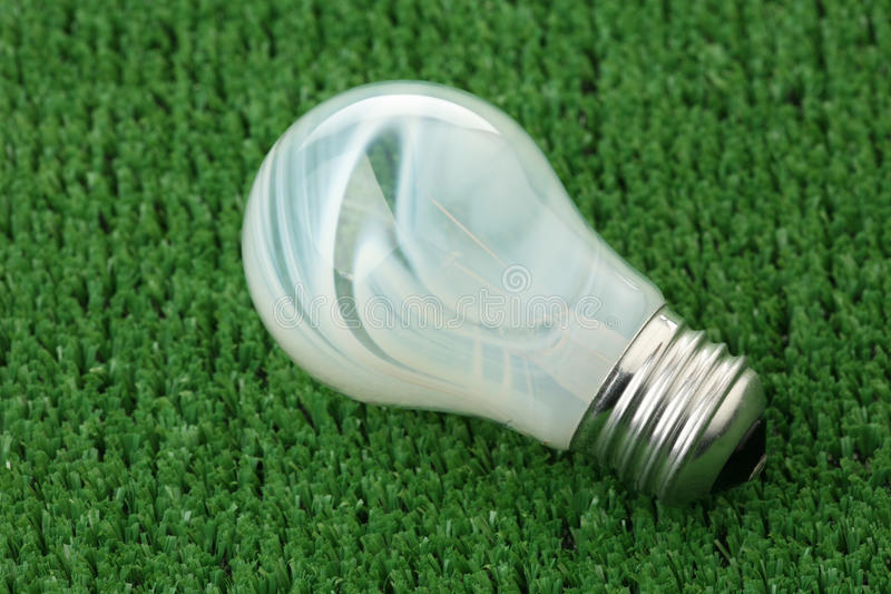 The bulb has fused. On a green background of artificial grass stock photo
