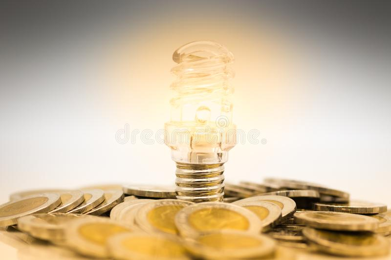 The bulb is placed stack of coins, the bulb is lit in darkness. Image use for finding a way out in the dark royalty free stock photo