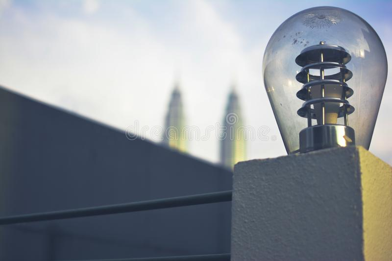 Bulb with sunset and blur twin tower. Good balance and have space in the left royalty free stock photo