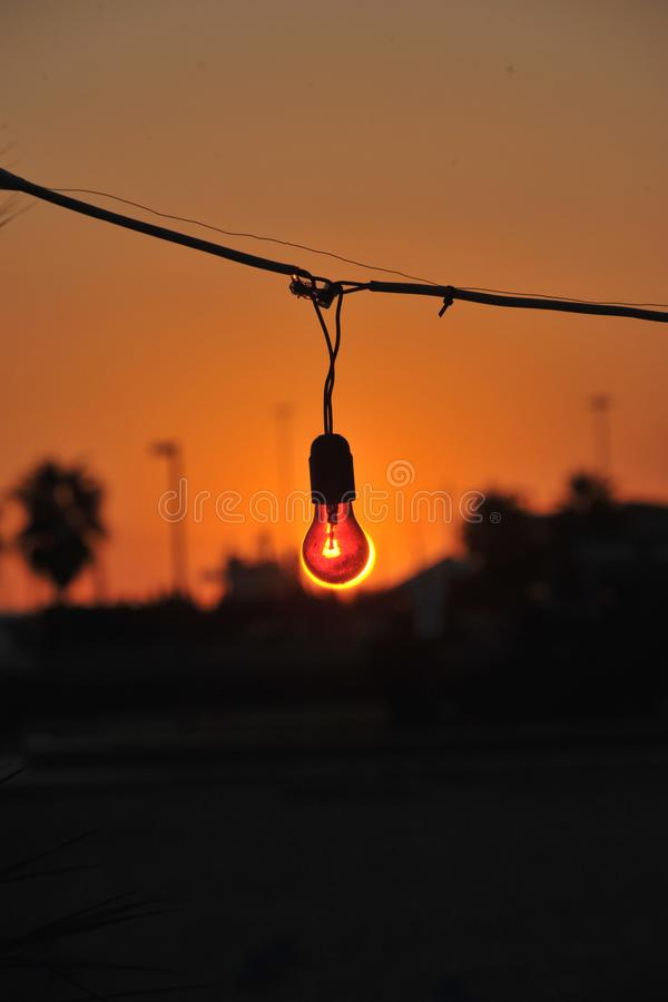 Bulb at sunset. Sunlight reflex in a bulb orange and black creates a special effect of daylight-powered light bulb