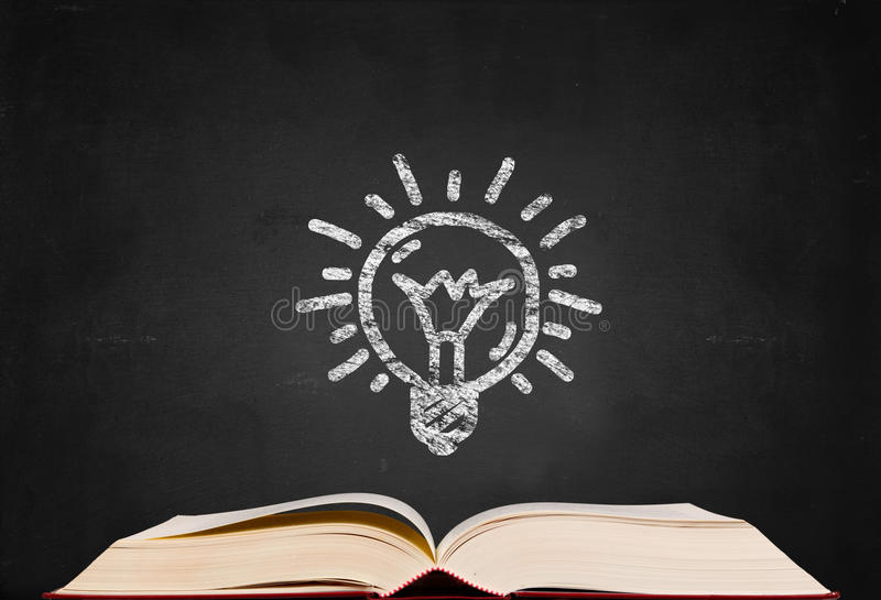 Bulb symbol and text book on blackboard stock photography