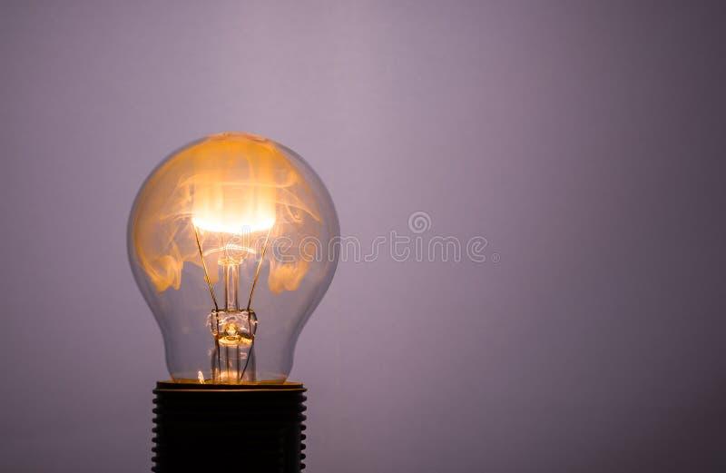 Bulbo de cristal con el fuego anaranjado dentro del alambre ligero foto de archivo