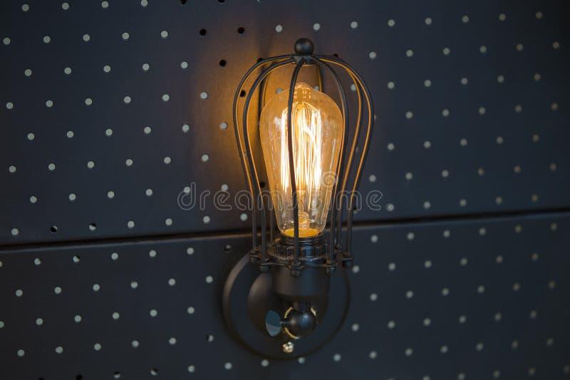 Bulbo de Edison de la lámpara del vintage, lámpara de pared en un panel negro del metal fotografía de archivo libre de regalías