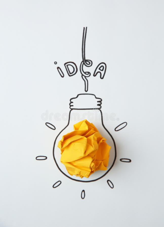 Bulbo de lámpara exhausto, papel arrugado y palabra IDEA en blanco foto de archivo libre de regalías