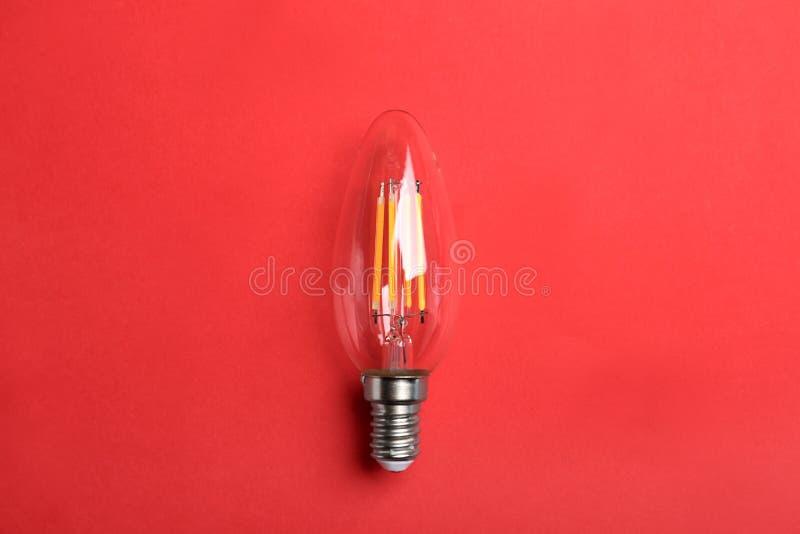 Bulbo de lámpara de filamento del vintage en fondo rojo foto de archivo libre de regalías