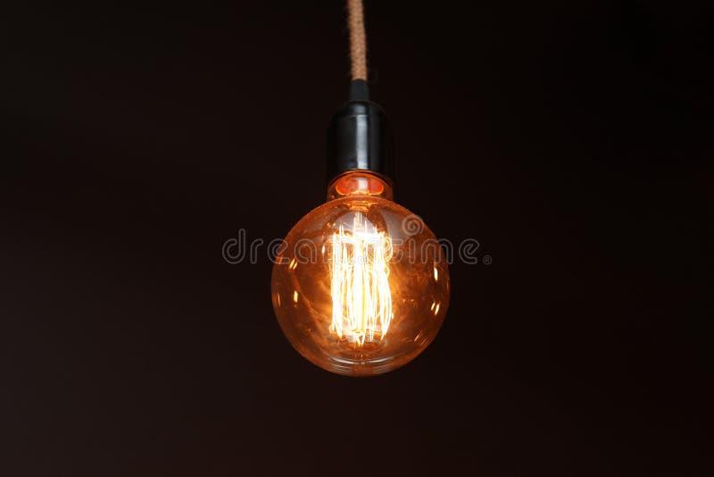 Bulbo de lámpara que brilla intensamente en oscuridad foto de archivo