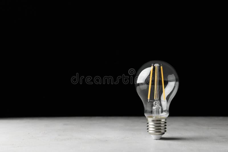 Bulbo de lâmpada do vintage na tabela clara contra o fundo preto fotos de stock royalty free