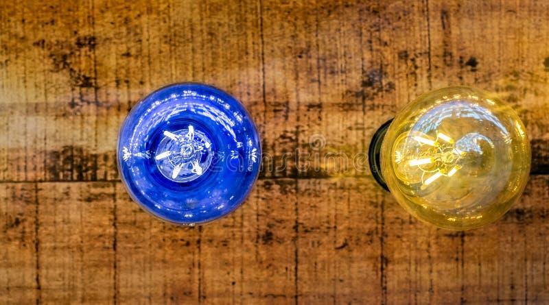 Bulbo de la luz ámbar azul y en el fondo de madera fotos de archivo