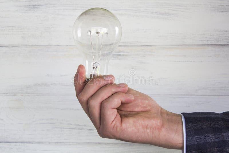 Bulbo de la luz eléctrica en el ` s del hombre de negocios foto de archivo
