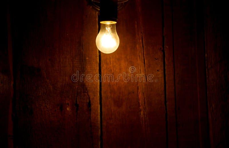 Bulbo de la luz eléctrica en fondo de madera fotografía de archivo libre de regalías